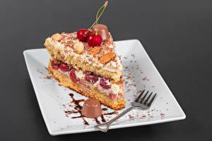 Фото Пирожное Конфеты Шоколад Вишня Торты Сером фоне Тарелке Вилки Кусок Пища