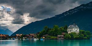 Фотографии Швейцария Горы Озеро Здания Лодки Альпы Облака Lake Brienz Природа
