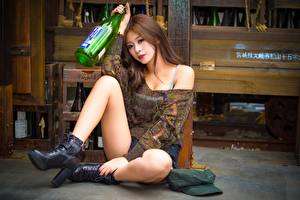 Картинки Азиатка Шатенки Бутылки Рука Ног Сидящие молодая женщина