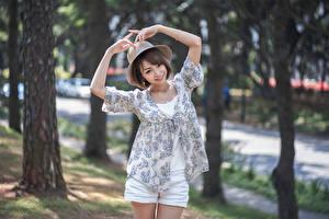 Фото Азиаты Позирует Шляпы Рука Улыбается Боке молодые женщины