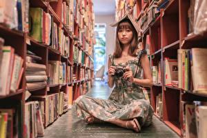 Фотографии Азиатка Сидит Платья Книги Фотоаппарат Смотрят Библиотека молодая женщина