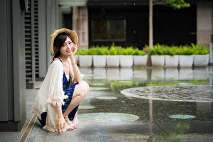 Картинки Азиаты Сидящие Шляпы Смотрят молодая женщина