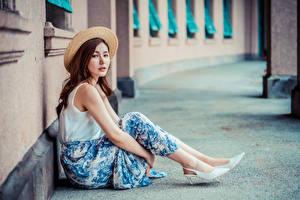 Картинки Азиаты Сидящие Юбка Шляпа Смотрят молодая женщина
