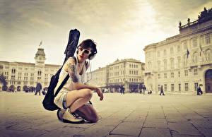 Фотографии Франция Городская площадь Париже Брюнетка Наушники Очки Гитара Сидит молодые женщины