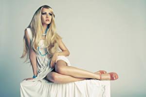 Картинки Ожерелье Сером фоне Блондинка Платье Сидящие Руки Позирует Ног Девушки