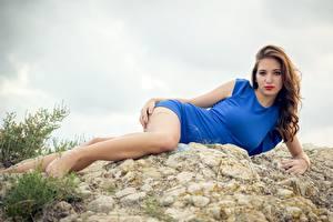 Картинки Камень Шатенка Платье Лежит Рука Ног молодая женщина