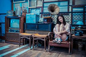 Фотография Азиатка Кресло Сидит Ног Взгляд Телефона ТВ Лампы Грампластинки девушка