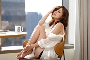Фотография Азиатка Размытый фон Сидит Ноги Взгляд молодые женщины