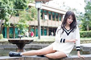 Фото Азиаты Размытый фон Сидящие Свитера Руки Ног Девушки