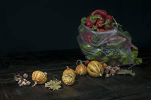 Фотографии Перец овощной Тыква Орехи Черный фон Листья Продукты питания