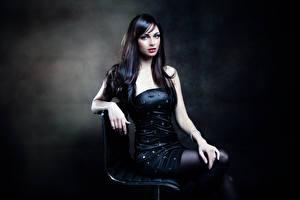 Фотографии Брюнетка Платье Взгляд Рука Сидит молодые женщины