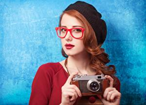 Картинки Рыжие Берет Смотрят Очки Руки Фотоаппарат Фотограф Цветной фон Девушки
