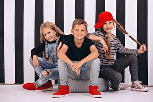 Фотография Трое 3 Сидит Мальчики Девочка Взгляд Кепка Джинсы Дети