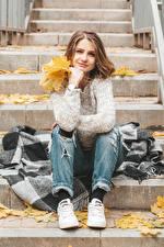 Фотография Осенние Шатенки Сидящие Листва Взгляд Свитере молодые женщины