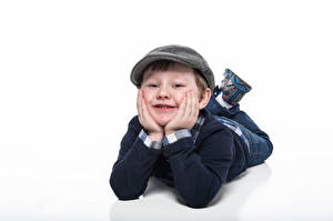 Фотографии Мальчишка Лежа Кепкой Улыбка Взгляд Белый фон ребёнок