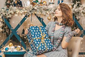 Фотография Рождество Шатенки Подарки Сидя Шарфе Руки Ветвь Шар молодая женщина