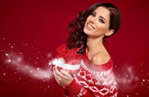 Фото Новый год Izabela Magier Подарки Свитера Взгляд Улыбка Красный фон молодая женщина