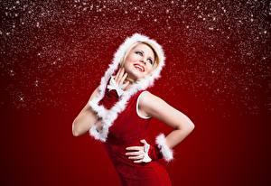 Фото Рождество Позирует Улыбается Рука Капюшоне Красном фоне молодая женщина