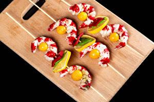 Фото Креветки Лимоны Томаты Черный фон Разделочной доске Еда