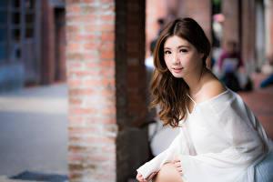 Фото Азиаты Шатенки Смотрит Размытый фон Рука девушка