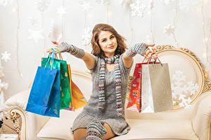 Обои для рабочего стола Новый год Шатенки Сидящие Подарок Улыбка Рука Бумажный пакет Платье Покупки молодые женщины