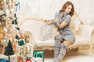 Фотографии Новый год Шатенки Сидит Улыбается Платья Подарков Новогодняя ёлка Диване молодая женщина