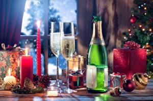 Фото Новый год Игристое вино Свечи Огонь Бокалы Бутылки Подарки