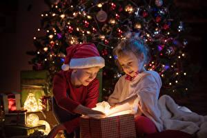 Картинки Рождество Новогодняя ёлка Электрическая гирлянда Два Мальчик Девочка Шапки Подарок Дети