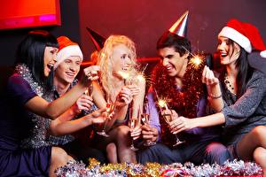 Обои для рабочего стола Рождество Мужчина Шапки Блондинки Сидит Смеется Радость Рука Бенгальские огни Бокалы девушка