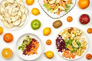 Фото Фрукты Мандарины Яблоки Лимоны Киви Гранат Белый фон Тарелка Нарезанные продукты Еда