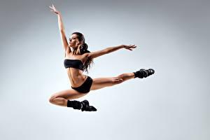 Обои Сером фоне В прыжке Танцует Поза Рука Ног девушка