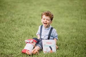 Картинка Смех Мальчишка Трава Сидящие Книги ребёнок