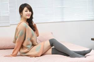 Картинки Азиатки Постель Шатенка Улыбается Свитера Сидя Ноги Гольфах молодые женщины