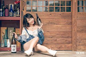 Фото Азиатки Бутылка Брюнетка Сидит Улыбка Ног молодая женщина