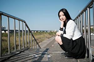 Картинки Азиаты Брюнетка Поза Сидит Униформа Школьница Взгляд девушка