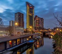 Картинка Голландия Вечер Здания Мосты Лодки Водный канал The Hague Города
