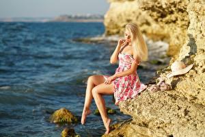 Картинка Море Блондинка Платье Скалы Шляпе Сидящие Ног молодая женщина