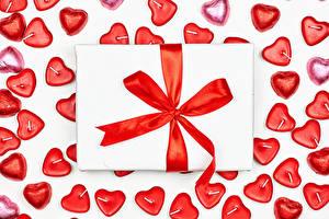 Фото День святого Валентина Конфеты Свечи Белый фон Подарки Бантик Серце