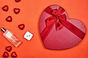 Фотографии День всех влюблённых Конфеты Цветной фон Подарки Сердце Бантик Парфюм Красный фон Еда