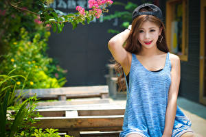 Фото Азиаты Размытый фон Кепкой Смотрят Улыбка Рука Сидя молодые женщины