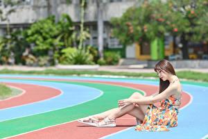 Фото Азиаты Размытый фон Шатенка Сидит Платье Руки Ног девушка