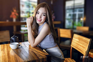 Обои Азиатки Размытый фон Сидит Кафе Чашка Шатенка Взгляд Улыбка Руки молодые женщины