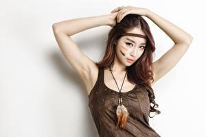 Обои Азиаты Серый фон Шатенка Смотрят Мейкап Руки Красивые молодые женщины