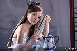Картинка Азиатка Чайник Размытый фон Шатенки Взгляд Руки молодые женщины