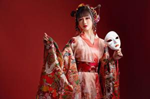 Фотографии Азиаты Маски Кимоно Смотрит Красный фон девушка