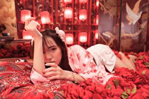 Фото Азиаты Лепестков Лежа Рука Взгляд молодая женщина