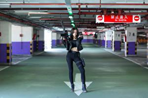 Картинки Азиатка Винтовки Пистолетом Позирует Куртка Взгляд молодая женщина