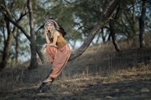 Обои для рабочего стола Перья Индейский головной убор Блондинок Размытый фон Позирует Сидящие Деревья Индеец Vicky молодые женщины
