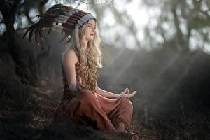 Картинки Поза лотоса Перья Индейский головной убор Блондинки Сидя Боке Vicky девушка