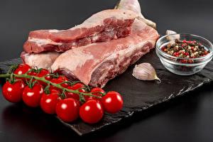 Фотография Мясные продукты Помидоры Перец чёрный Чеснок Свинина Серый фон Разделочная доска